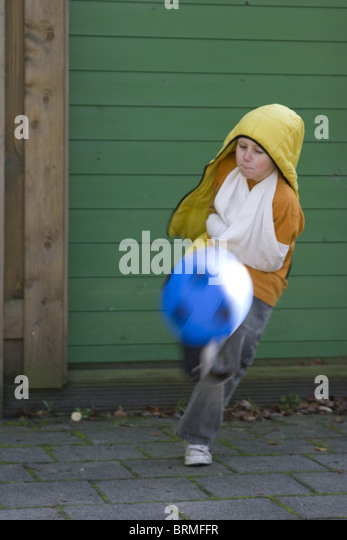 Rude young boy showing disrespect, kicking soccer ball, almost knocks me out. - Stock Image