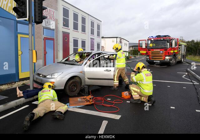 Firefighters working at the scene of an accident demonstration, UK. 'Car crash' scene, RTA or RTC, Crashed - Stock Image