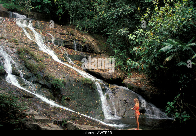 BELIZE Woman at Waterfall - Stock Image