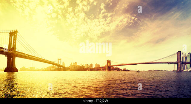 Vintage toned dramatic sunset over New York, panorama with famous Brooklyn Bridge and Manhattan bridge, USA. - Stock-Bilder