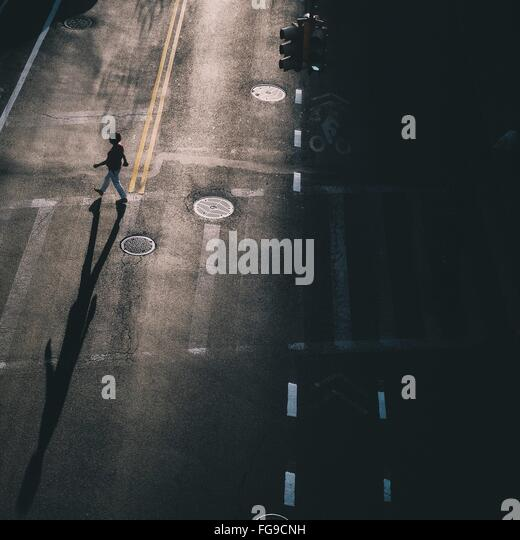 High Angle View Of Woman Crossing City Street - Stock Image