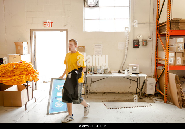 Worker carrying frame and t-shirt in screen printing workshop - Stock-Bilder