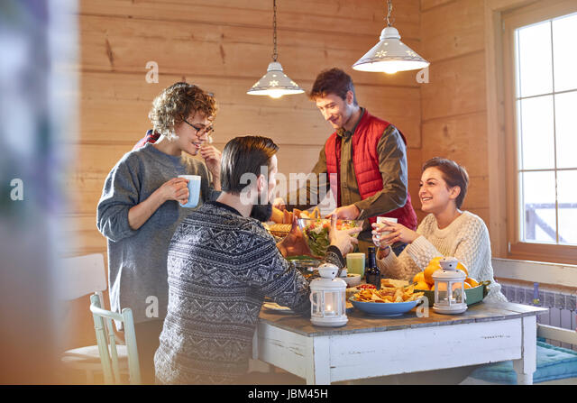 Friends eating and talking at cabin table - Stock-Bilder