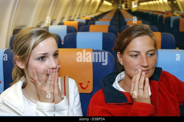 (dpa) - Two young ladies sit tense and strained on their seats in a chartered aircraft at the airport in Bremen, - Stock Image