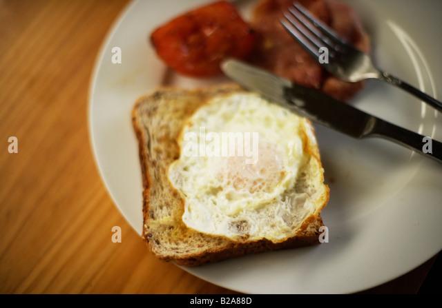 Bacon tomato and fried egg on toast - Stock Image