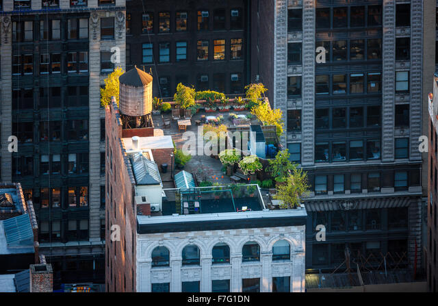Aerial view of a Manhattan rooftop in the heart of New York City. Roof garden in Chelsea with sunlit trees and wooden - Stock Image