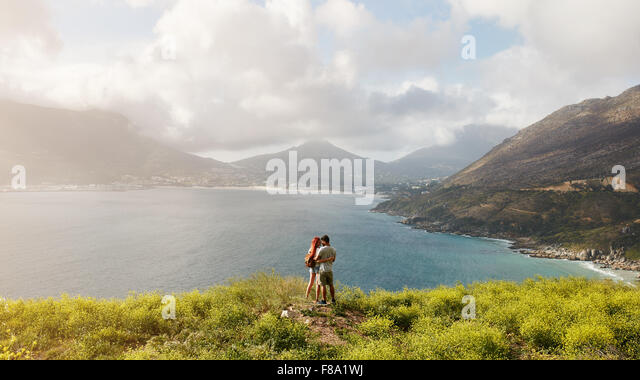 Young couple in love standing on hill, with beautiful view of bay and mountain range in background. Couple on romantic - Stock-Bilder