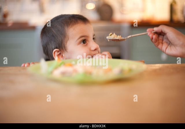 3 year old boy sitting at table with hand holding food on spoon - Stock-Bilder