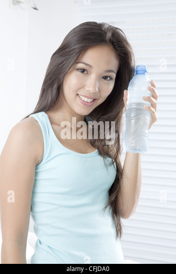 Young woman holding bottled water - Stock Image