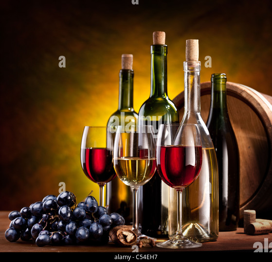 Still life with wine bottles, glasses and oak barrels. - Stock Image