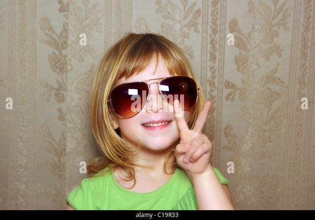 hand victory gesture little girl funny sunglasses retro wallpaper - Stock-Bilder