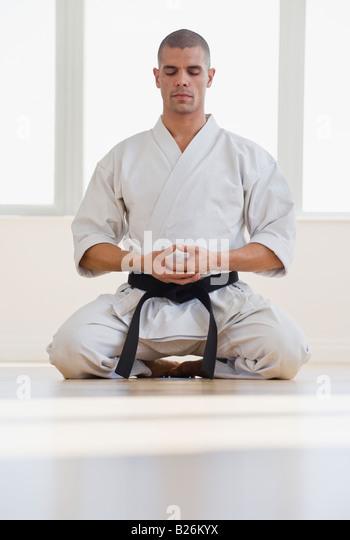Hispanic male karate black belt meditating - Stock Image