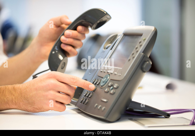Close-up of hands businessman take the phone of the hook, in office - Stock Image