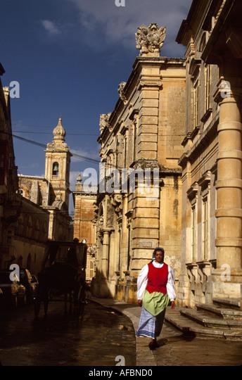 Malta Mdina Villagagnion Street Carmelite Church built 1630 female resident traditional costume - Stock Image