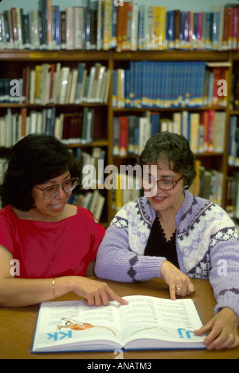 New Jersey Teaneck library volunteer teaches English Asian woman immigrant book pointing - Stock Image