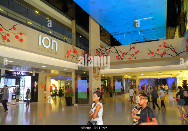 Singapore Orchard Road Ion Orchard mall complex shopping upscale Asian boy woman Chanel inside interior - Stock Image