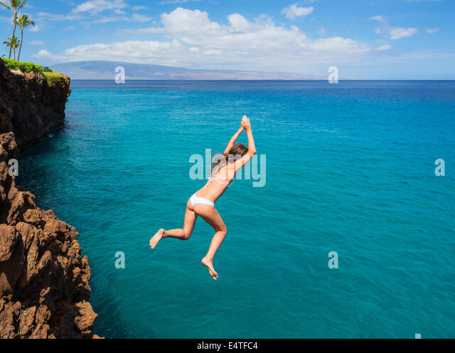 Woman jumping off cliff into the ocean. Summer fun lifestyle. - Stock Image