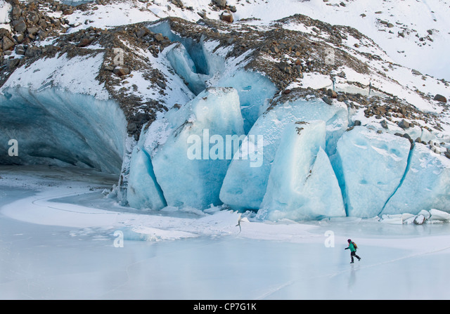 Woman ice skating in front of Saddlebag Glacier, Chugach Mountains near Cordova, Southcentral Alaska, Winter - Stock Image