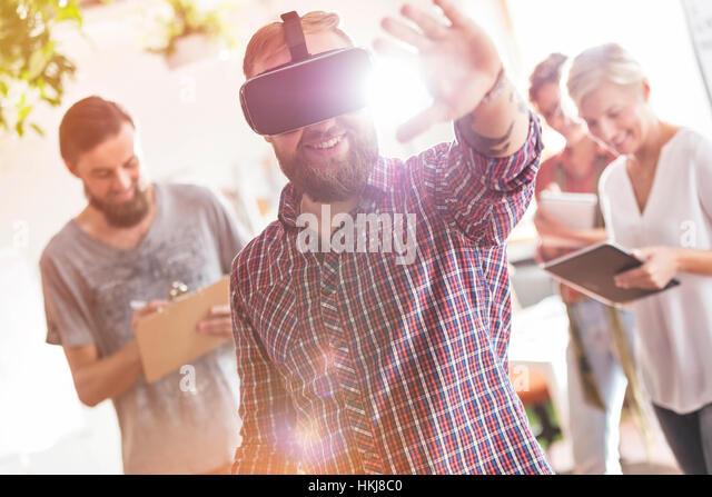 Smiling male design professional using virtual reality simulator glasses in meeting - Stock-Bilder