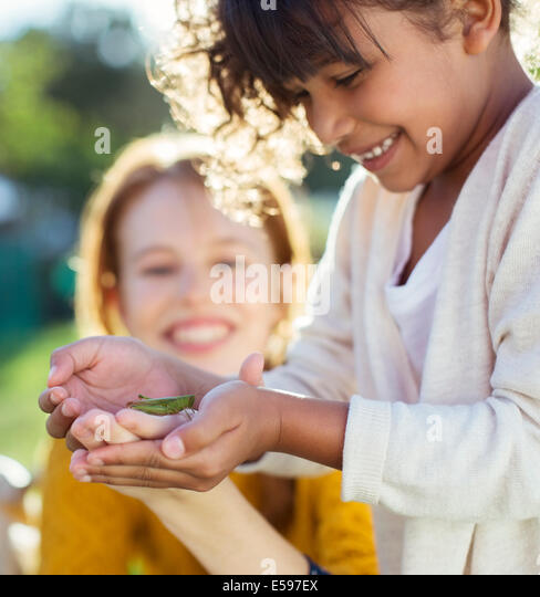 Mother and daughter examining insect - Stock Image