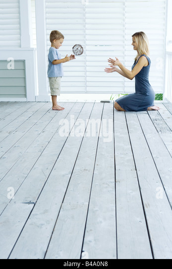 Mother and son playing catch on porch - Stock-Bilder