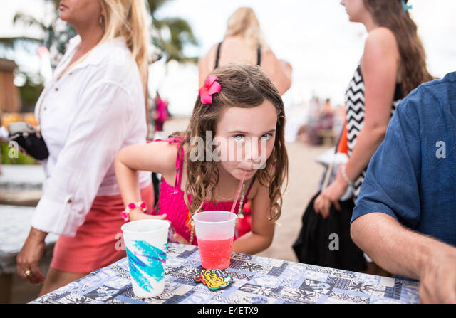Girl with flower in her hair sips tropical drink looking at camera. - Stock Image