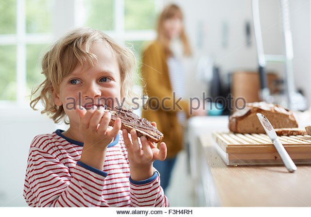 Young boy eating bread with chocolate spread, mother in background - Stock Image