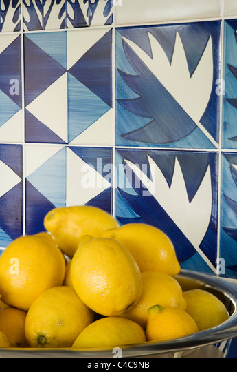 close-up of a bowl of lemons in front of contemporary blue and white tiling - Stock Image