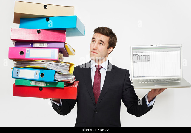 Businessman with stacks of folders and laptop - Stock-Bilder