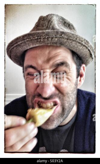 Guy eating a hot pepper - Stock Image