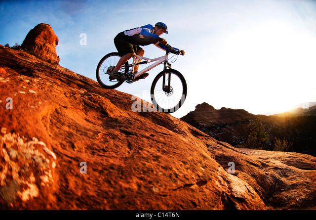 A middle age man rides his mountain bike through the red rock country around Sedona, Az at sunset. - Stock-Bilder