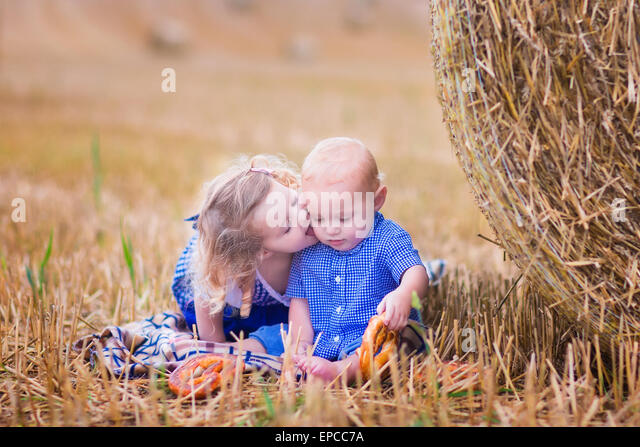 Two children, funny curly toddler girl and a little baby boy, wearing tradtional German costumes playing in a field - Stock Image