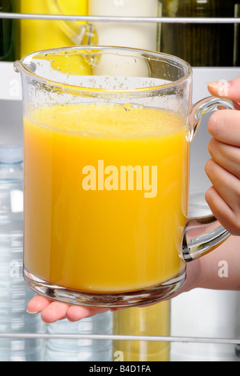 PUTTING JUG OF ORANGE JUICE IN FRIDGE - Stock Image