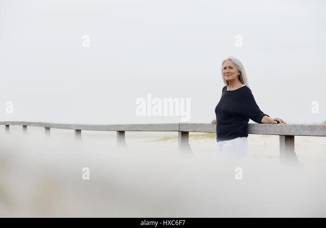 Confident senior woman leaning on beach boardwalk railing - Stock Image