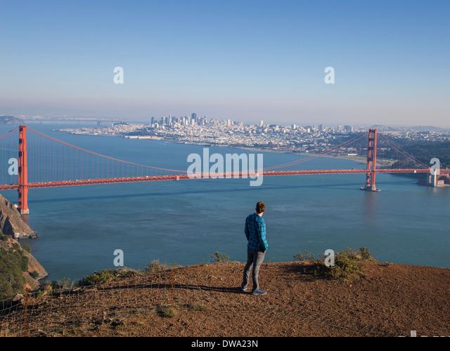 Young male tourist looking at Golden gate bridge, San Francisco, California, USA - Stock Image