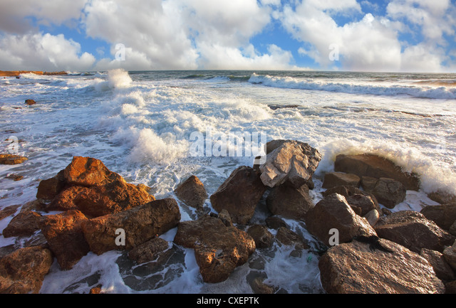 The waves crash against the rocks - Stock Image