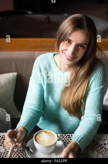 Charming woman in a restaurant. Pretty smiling caucasian girl enjoying her cappuccino in a cafe - Stock Image