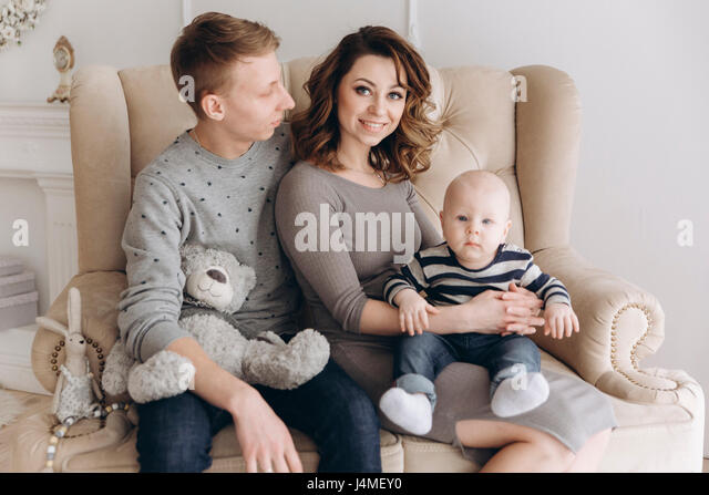 Portrait of Caucasian mother and father on love seat with baby son - Stock-Bilder