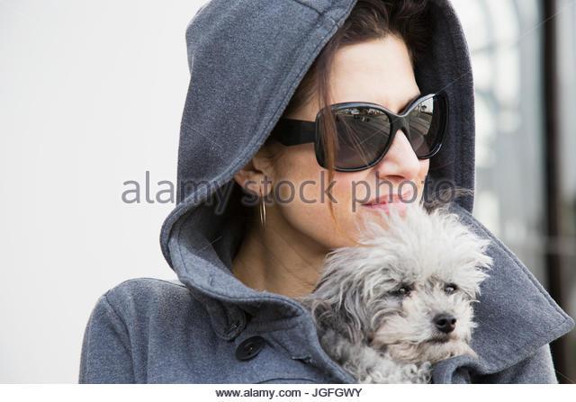 Caucasian woman holding dog in coat - Stock Image