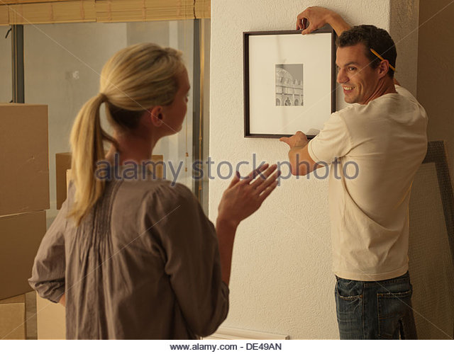 Couple hanging picture in new house - Stock Image