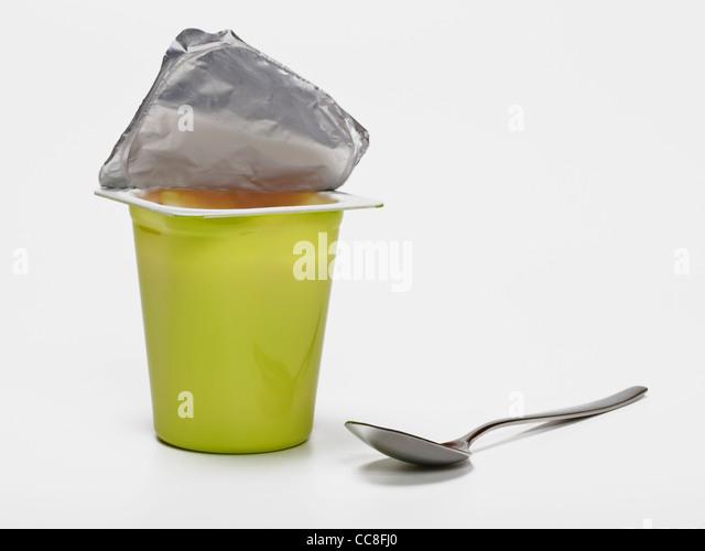 Detailansicht eines Joghurtbechers, daneben liegt ein kleiner Löffel | Detail photo of a yogurt cup, alongside - Stock Image