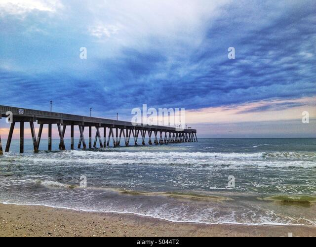 A fishing pier extends out into the Atlantic Ocean - Stock Image
