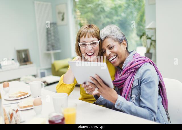 Laughing mature women sharing digital tablet at breakfast table - Stock-Bilder
