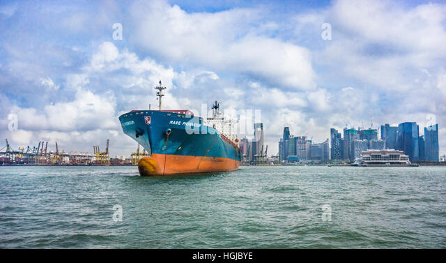 container ship Mare Phoenicium moored at the Port of Singapore with view of the Singapore skyline and Marina Bay - Stock Image