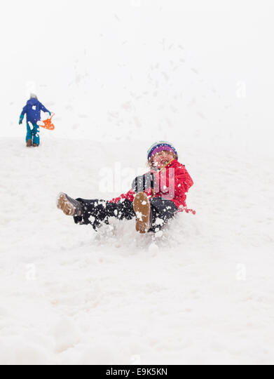 small girl sledging fast down a steep hill in a cloud of snow with small boy walking up hill in background - Stock Image