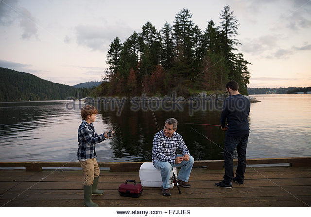 Multi-generation men fishing on lake dock - Stock Image