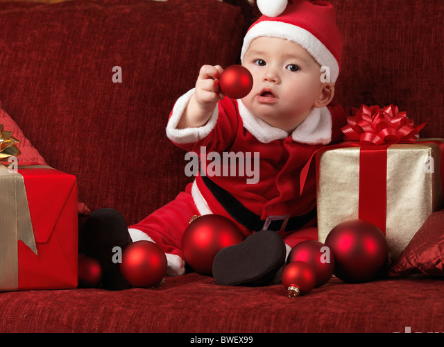 Six month old baby boy wearing Santa Christmas costume and holding a red bauble in his hand - Stock Image