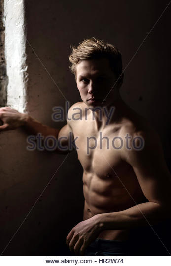 Shirtless young man near a window - Stock Image