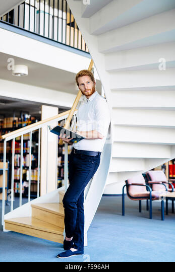 Handsome smart guy reading a book in a library - Stock Image
