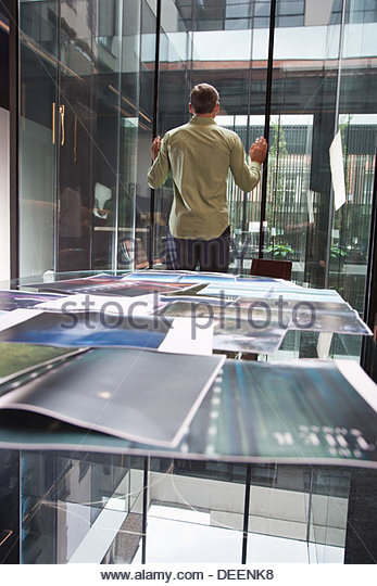 Businessman looking out large interior windows of office - Stock Image